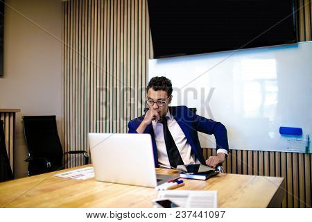 Serious Man Entrepreneur Studying Financial Information From Laptop Computer During Work Day In Offi