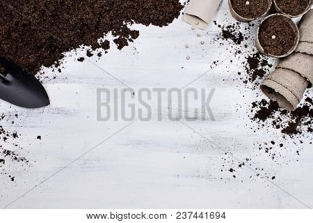 Gardening Tools, Seedling Peat Pots, Seeds And Soil On A White Wooden Table. Image Shot From Above I