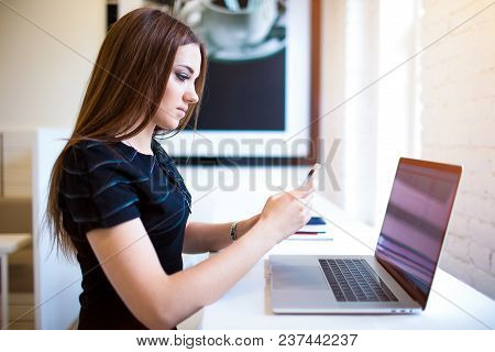 Woman Copywriter Reading Text Message In Notification Via Mobile Phone During Distance Work On Lapto
