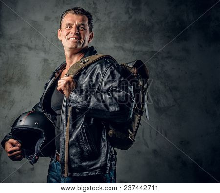 Portrait Of A Middle Age Male Dressed In A Leather Jacket Holds Motorcycle Helmet Over Grey Backgrou