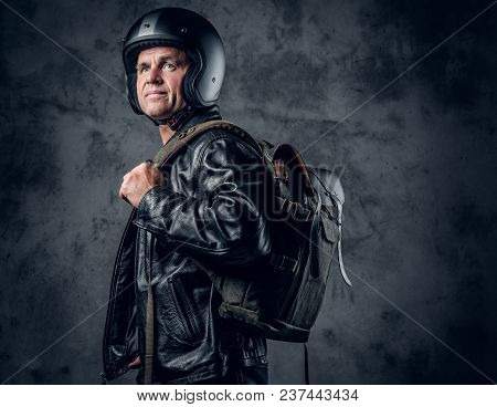 Middle Age Male In Motorcycle Helmet And Leather Jacket With Rucksack Smoking A Cigarette On Grey Ba