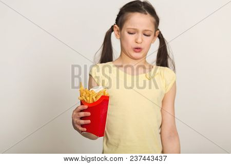 Disgusted Little Girl Holding A Bag Of Fries Isolated On White Background. Fast Food Against Healthy
