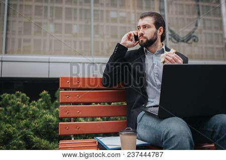Busy Man Is In A Hurry, He Does Not Have Time, He Is Going To Eat Snack Outdoors. Worker Eating And