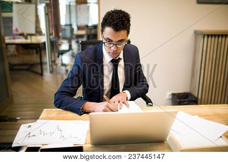 Man Intelligent Economist Writing Notary In Textbook During Work On Portable Laptop Computer. Male C