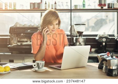 Middle-aged Barista Or Manager Working On Laptop And Talking On Smartphone, Accepting An Order At Mo