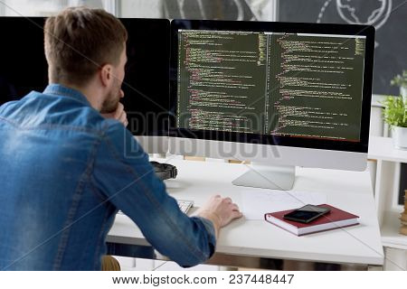 Rear View Of Concentrated Thoughtful Male Programmer Viewing Computer Language Code On Computer Moni