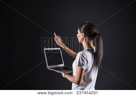 Progressive Developments. Smart Pleasant Brunette Woman Holding Her Laptop And Looking At The Finger