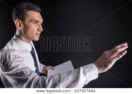 Modern Age. Nice Pleasant Handsome Man Holding A Tablet And Touching The Sensory Technology