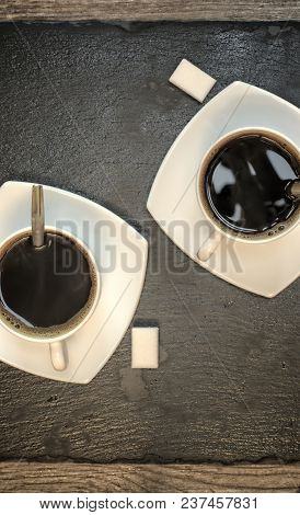 Drinks, Drinking, Energy And Caffeine Concept-two Cups Of Coffee On A Dark Slate Stand And Wooden Ba