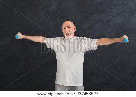 Senior Fitness Man Training With Dumbbells At Gym, Doing Strength Exercise For Biceps, Black Backgro