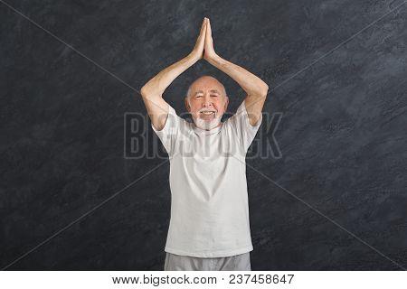 Sporty Mature Guy Practicing Yoga. Senior Man Doing Breathing Exercise Indoors, Black Background. Ac