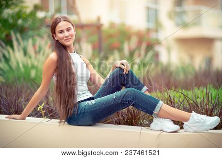 Beautiful young woman with pleasure spending time outdoors, student girl with natural makeup resting in the park, genuine womens beauty