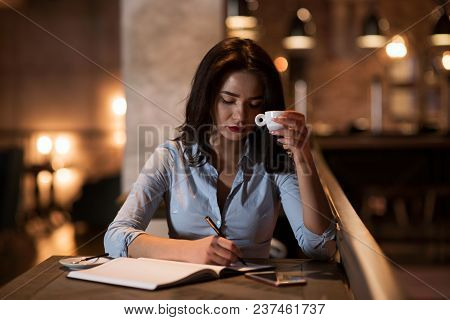 The Portrait Of An Elegant , Concentrated Businesswoman Drinking Coffee And Writing The Notes In Mod