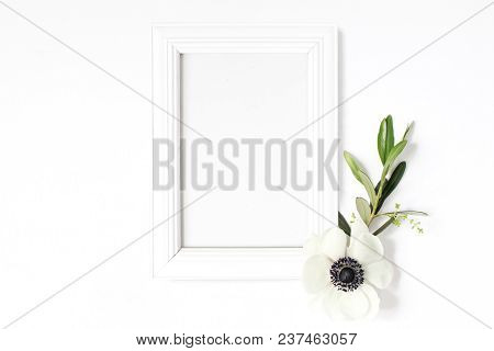 White Blank Wooden Picture Frame Mockup With Green Olive Branch And Anemone Flower Lying On The Whit