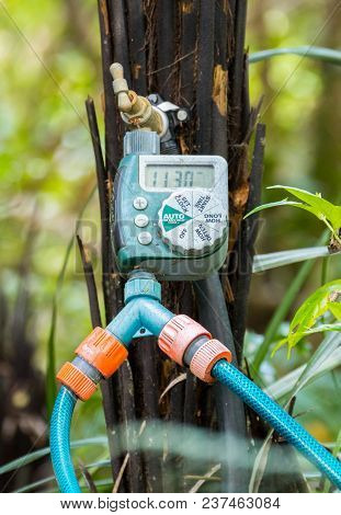 Water Time Controler With Two Hoses Conected To It.