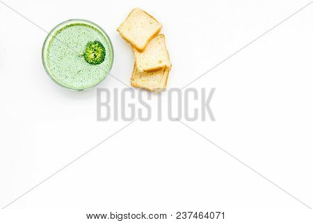 Green Broccoli Cream Soup With Broccoli Served With Rusks And Greens On White Background Top View.