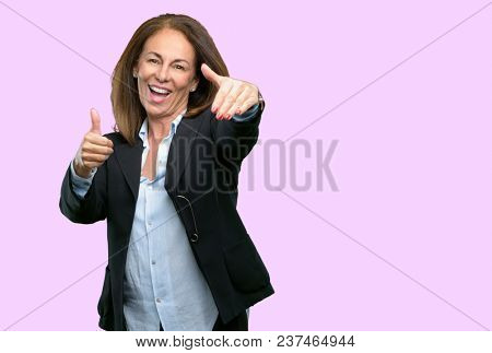 Middle age business woman stand happy and positive with thumbs up approving with a big smile expressing okay gesture