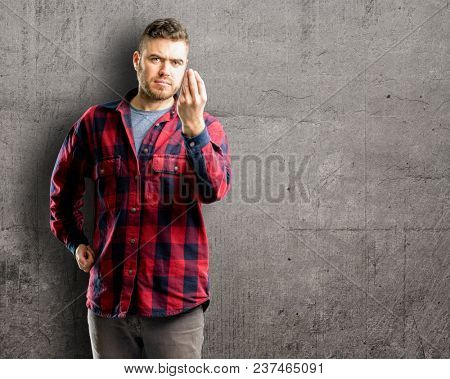 Young handsome man angry gesturing typical italian gesture with hand, looking to camera