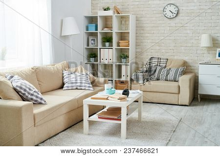 Modern Living Room With Simple Interior Design, Clock Hanging On Brick Wall, Shelves With Home Staff