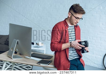 Young Man Holding Camera And Leaning On Table With Computer At Home Office