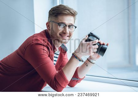 Young Bearded Man In Glasses Holding Camera By Window