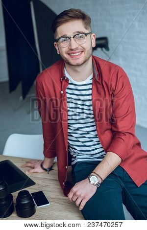 Smiling Young Man Leaning On Table With Camera Lenses