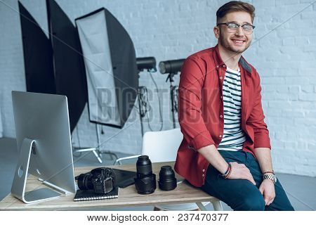 Smiling Photographer Sitting On Table With Camera And Computer