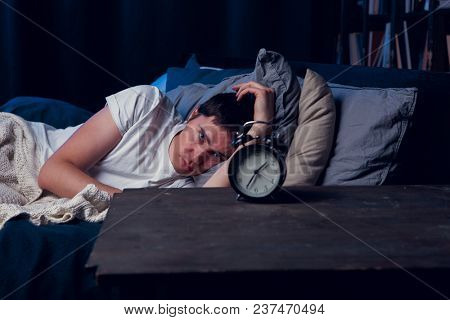 Image of brunet with insomnia lying in bed with alarm clock