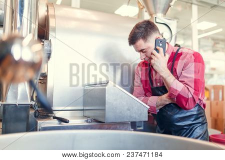Image of businessman talking on phone at computer of industrial machine