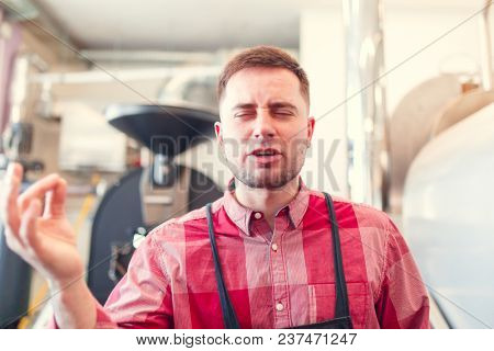 Photo of happy barista in apron on background of industrial coffee grinder