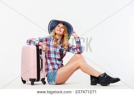 Portrait of woman in hat sitting near suitcase