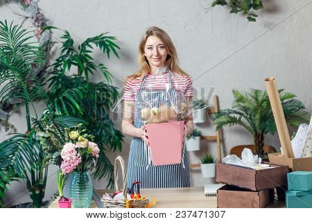 Photo of florist with floral composition in box at table with boxes, paper