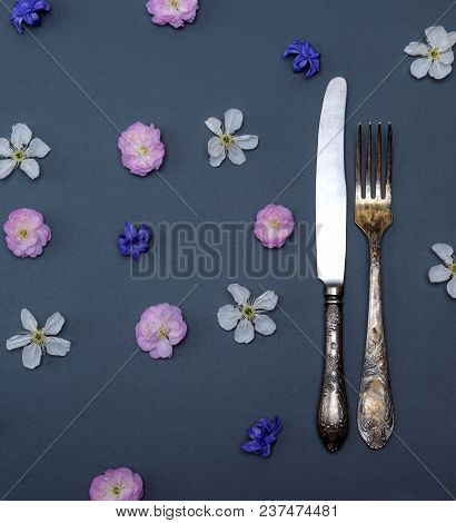 Iron Vintage Cutlery Fork And Knife On Black Background With Flower Buds, Top View