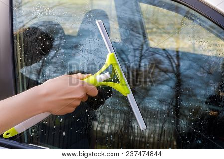 Hand Washer Washes A Window Of A Car.