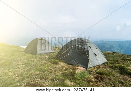 Tourist tents in camp among meadow in the mountain. Camping outdoor, tents in mountains