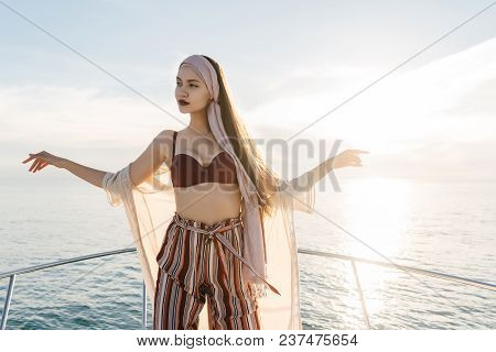 A Gorgeous Young Woman In Fashionable Pants Stands On Her Yacht In The Sun, Enjoys Sea Voyage