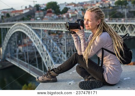 Young woman with camera sitting on the viewing platform opposite the Dom Luis I bridge across the Douro river, Porto, Portugal.