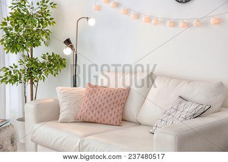 Elegant living room interior with comfortable sofa and stylish floor lamp