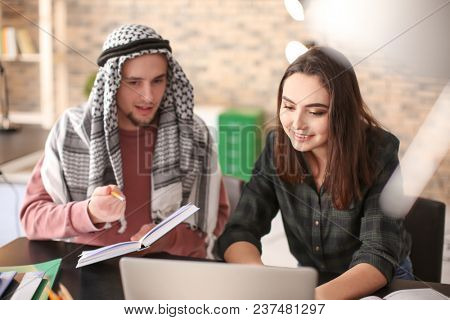 Female student with her Muslim classmate in library
