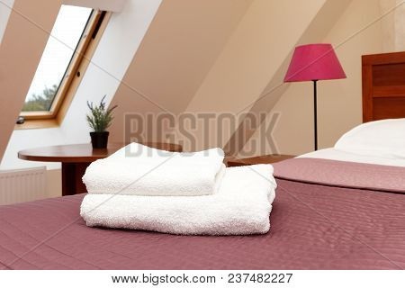 White Fluffy Towels Lie On The Bed In The Hotel Room.