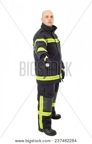 Serious firefighter with a flashlight. Full length studio shot isolated on white.