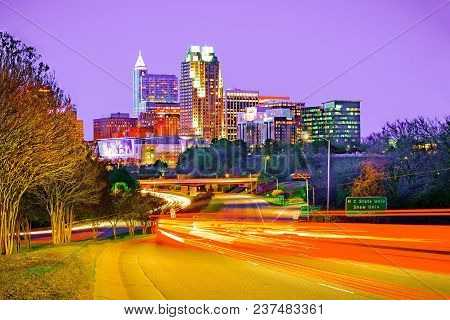 A beautiful cityscape view of downtown Raleigh, North Carolina at night with traffic trails.