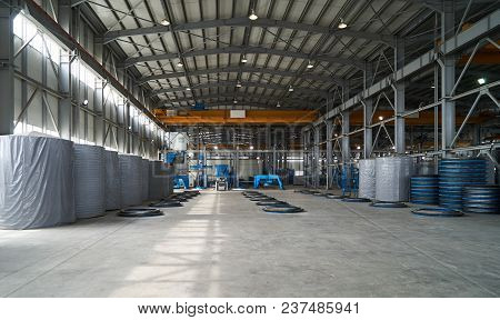 Modern Large Factory Warehouse Interior With Some Goods Concrete Pipes. Industrial Production Of Cem