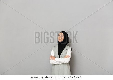 Portrait of a happy young arabian woman standing with arms folded and looking away isolated over gray background