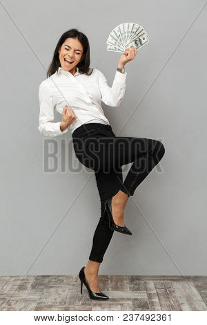 Full length portrait of a happy young businesswoman holding money banknotes and celebrating isolated over gray background