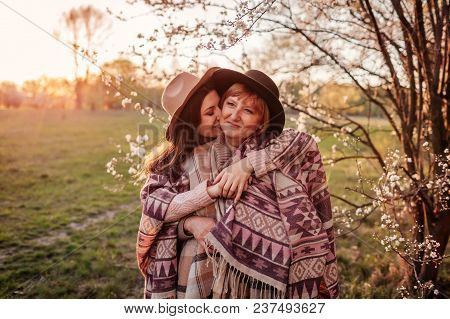 Middle-aged Mother And Her Adult Daughter Hugging In Blooming Garden. Mother's Day Concept. Family V