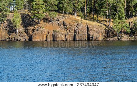 A View Of The Shore Of The Lake, Rocks And Pine Trees On The Shore. Summer Sunny Day