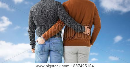 lgbt, same-sex relationships and homosexual concept - close up of hugging male gay couple over blue sky and clouds background