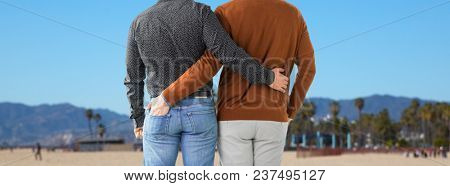 lgbt, same-sex relationships and homosexual concept - close up of hugging male gay couple over venice beach background in california