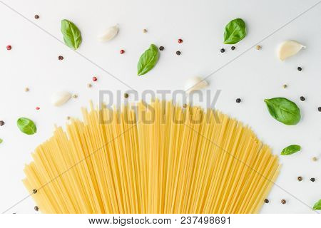 Concept Food With Pasta, Basil, Garlic And Pepper On A White Background. Bouquet Of Spaghetti And Sp